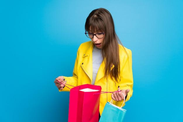 Junge frau mit gelber jacke auf der blauen wand überrascht beim halten vieler einkaufstaschen Premium Fotos