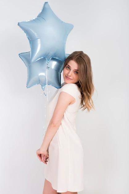 Junge frau mit glänzenden partyballonen Kostenlose Fotos
