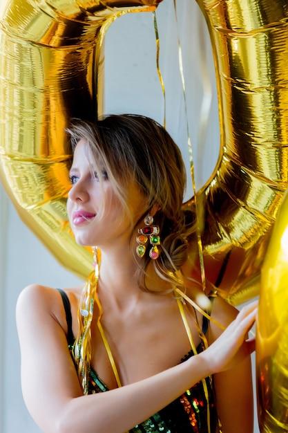 Junge frau mit goldenen ballonen nähern sich fenster Premium Fotos