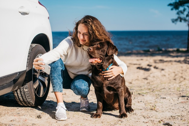 Junge frau mit ihrem hund am strand Kostenlose Fotos