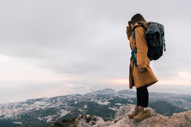 Junge frau mit ihrem rucksack, der auf die oberseite des berges idyllische ansicht betrachtend steht Kostenlose Fotos