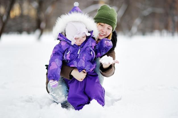 Junge frau mit ihrer kleinkindtochter, die mit schnee am winterpark spielt Premium Fotos