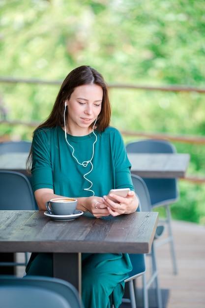 Junge frau mit intelligentem telefon beim in der kaffeestube während der freizeit allein sitzen Premium Fotos