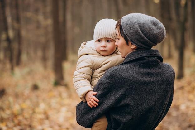 Junge frau mit kindern, die im herbstpark gehen Kostenlose Fotos