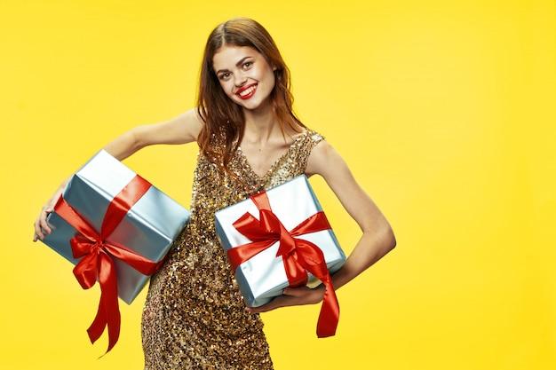 Junge frau mit kisten von geschenken in ihren händen in den schönen kleidern, verkaufende geschenke, frohe weihnachten und neujahr Premium Fotos