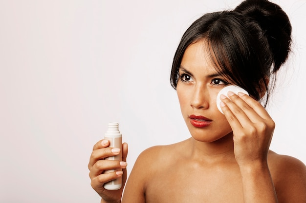 Junge frau mit kosmetik-lotion und wattepad Kostenlose Fotos
