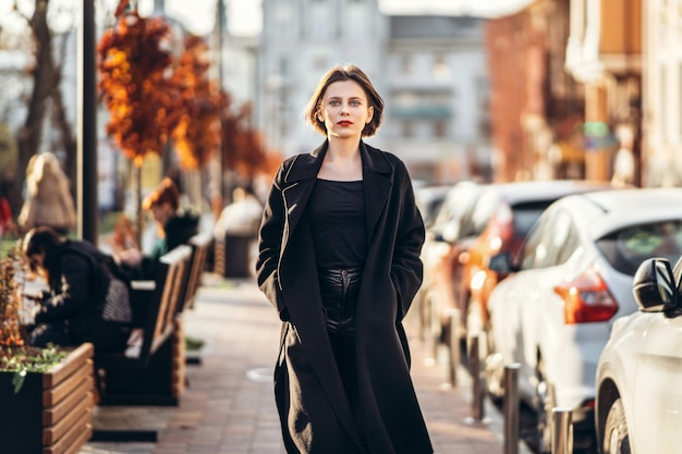 Junge frau mit kurzem haarschnitt, gekleidet in einen schwarzen mantel, der durch die straßen der stadt schlendert. herum sind menschen und autos. Premium Fotos