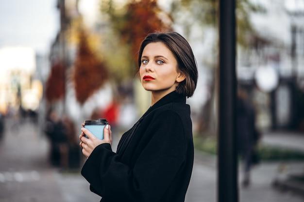 Junge frau mit kurzem haarschnitt und roten lippen, hält eine tasse kaffee im freien Premium Fotos