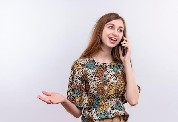 Junge frau mit langen haaren, die buntes kleid lächelnd beim sprechen auf handy tragen, das über weißer wand steht Kostenlose Fotos