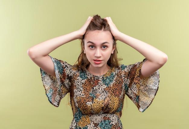 Junge frau mit langen haaren, die buntes kleid tragen, das gestressten und frustrierten berührenden kopf über grüner wand steht Kostenlose Fotos