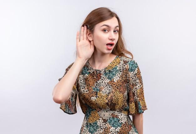 Junge frau mit langen haaren, die buntes kleid tragen, das mit hand nahe ohr steht und versucht, jemandes gespräch über weiße wand zu hören Kostenlose Fotos