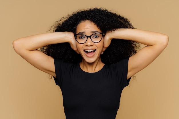 Junge frau mit lockigem afro-haar deckt die ohren ab, schreit, wenn es leise sein soll, und kann keinen lärm ertragen Premium Fotos