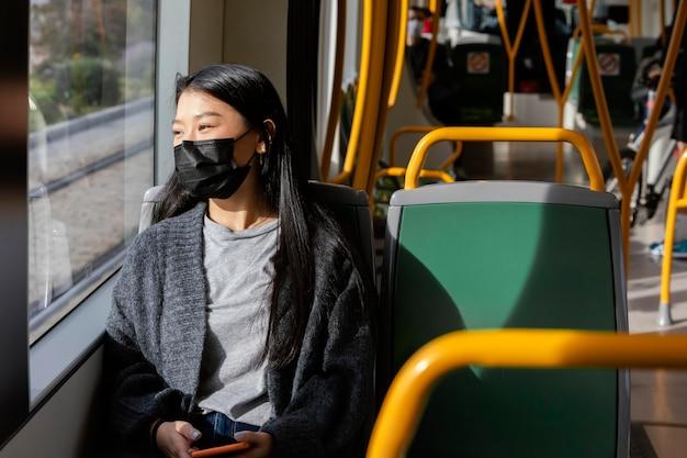 Junge frau mit maske im bus Kostenlose Fotos