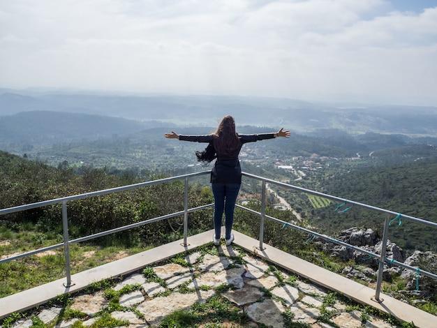 Junge frau mit offenen armen, die den schönen blick auf die berge genießen Kostenlose Fotos