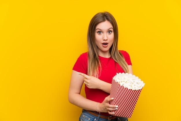 Junge frau mit popcorn über der rosa wand überrascht und seite zeigend Premium Fotos