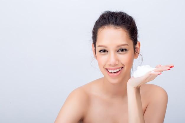 Junge frau mit reinigungsschaum für hautpflege auf weißem hintergrund Premium Fotos