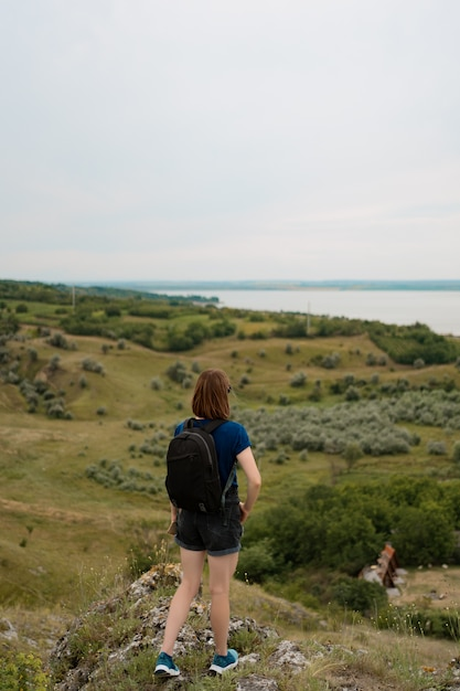 Junge frau mit rucksack, der auf klippenrand steht und zum himmel und zur schönen natur schaut. Kostenlose Fotos