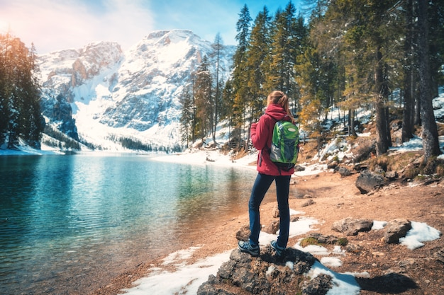 Junge frau mit rucksack steht auf dem stein nahe see mit azurblauem wasser am sonnigen tag im herbst Premium Fotos