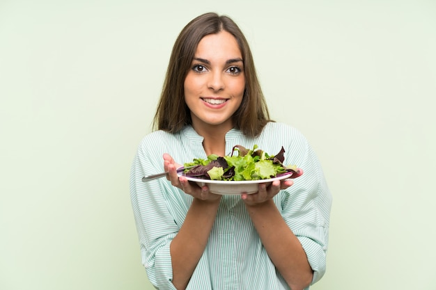 Junge frau mit salat über getrennter grüner wand Premium Fotos