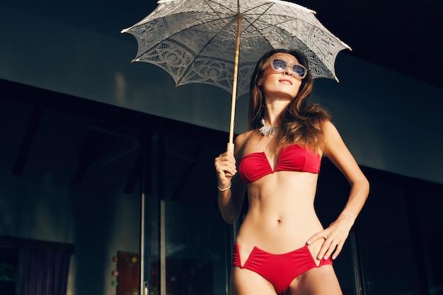 Junge frau mit schönem schlanken körper, der roten bikini-badeanzug trägt, der spitzen-sonnenschirm auf tropischem villenresort während der urlaubsreise in asien, dünne figur, sommerart-trendzubehör hält Kostenlose Fotos