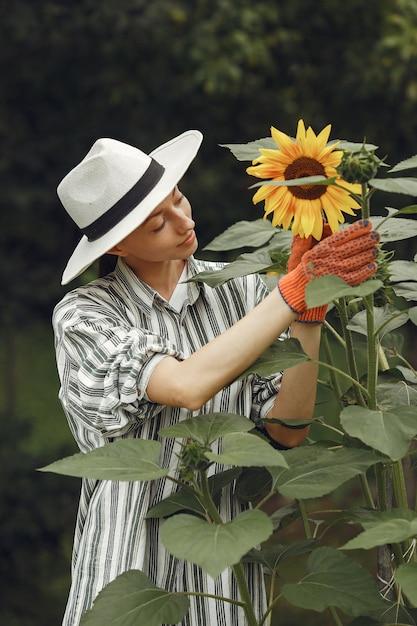 Junge frau mit sonnenblumen. dame mit hut. mädchen in einem garten. Kostenlose Fotos