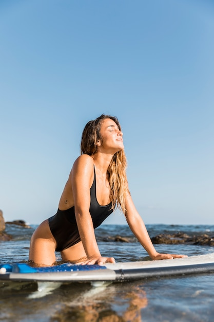 Junge frau mit surfbrett wetter genießen Kostenlose Fotos