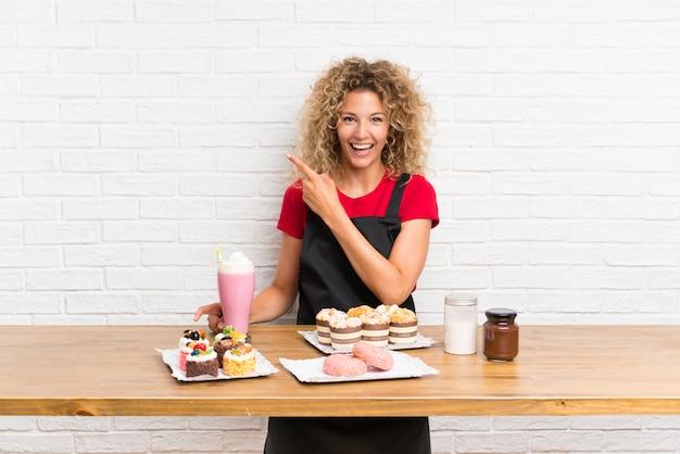 Junge frau mit vielen verschiedenen minikuchen in einer tabelle finger auf die seite zeigend Premium Fotos
