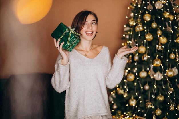 Junge frau mit weihnachtsgeschenk durch den weihnachtsbaum Kostenlose Fotos