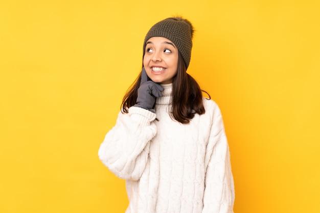 Junge frau mit winterhut über gelber wand eine idee beim oben schauen denkend Premium Fotos