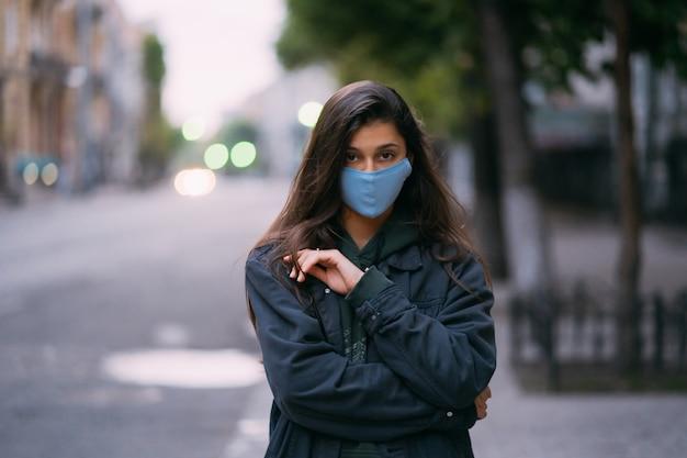 Junge frau, person in der medizinischen schutzsterilmaske an der leeren straße Kostenlose Fotos