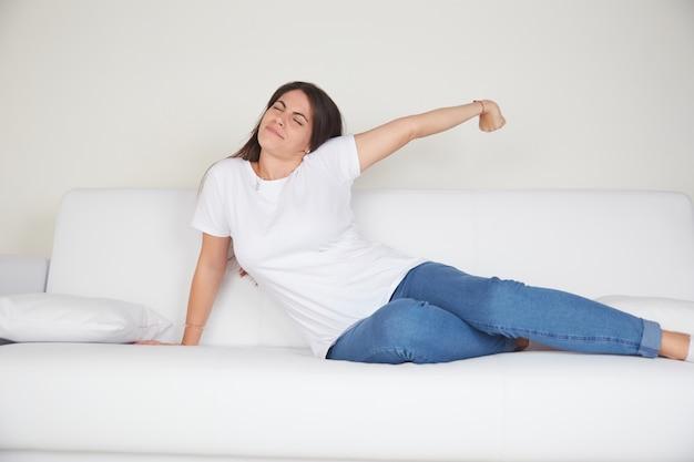 Junge frau ruhen auf dem sofa Premium Fotos
