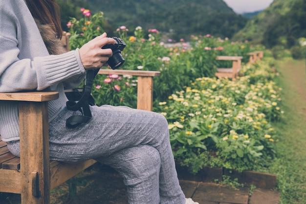 Junge frau sitzen auf hölzerner bank im park. Premium Fotos