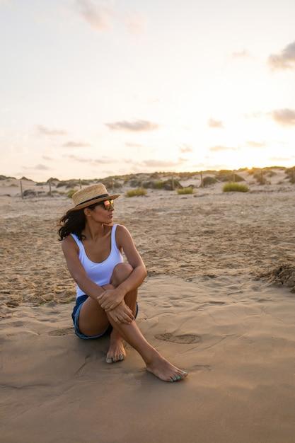 Junge frau sitzt am strand Premium Fotos