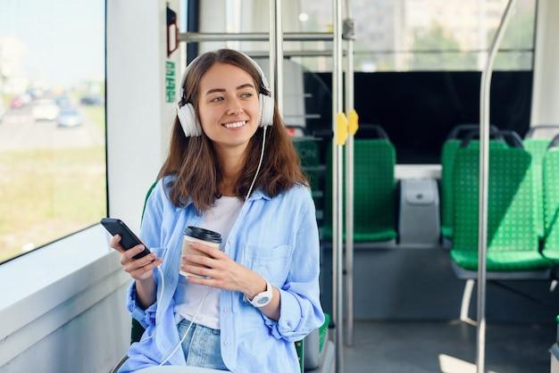 Junge frau sitzt im modernen stadtbus, hört musik, trinkt kaffee und schaut aus dem fenster. Premium Fotos