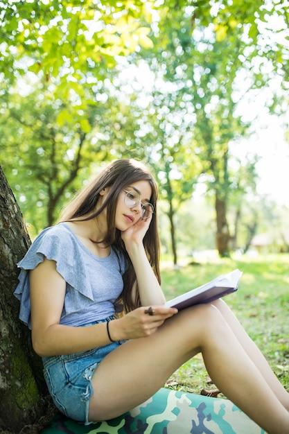 Junge frau sitzt und liest ihr lieblingsbuch auf ua grünem gras unter baum in einem schönen sonnigen sommer Kostenlose Fotos