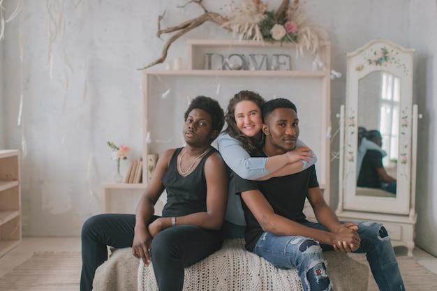 Junge frau sitzt und umarmt zwei männer zu hause Premium Fotos