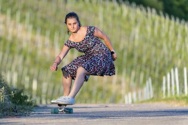 Junge frau skateboarding auf einer leeren straße, die durch grün umgeben ist Kostenlose Fotos