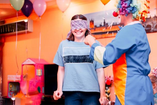 Junge frau spielt den blend des blinden mannes mit clown Premium Fotos