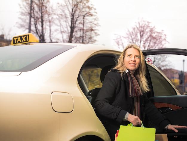 Junge frau steigt mit einkaufstüten aus dem taxi Premium Fotos