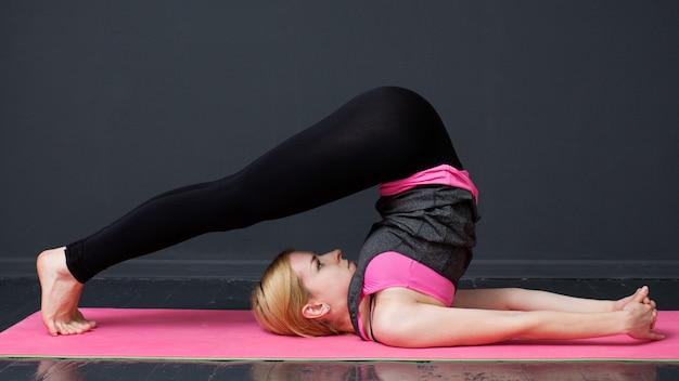 Junge frau tut yogatraining Premium Fotos