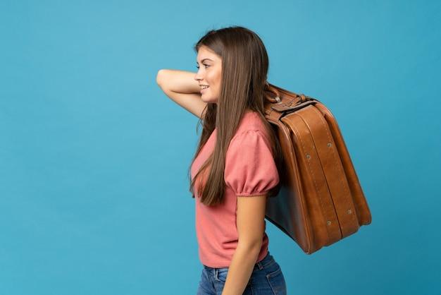 Junge frau über dem lokalisierten blau, das einen weinleseaktenkoffer hält Premium Fotos