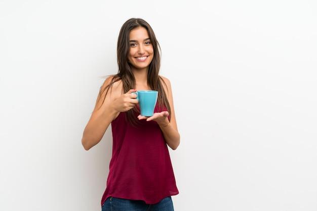 Junge frau über dem lokalisierten weiß, das heißen tasse kaffee hält Premium Fotos