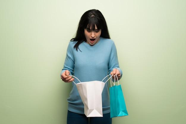 Junge frau über der grünen wand überrascht beim halten vieler einkaufstaschen Premium Fotos