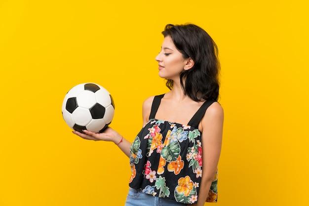Junge frau über der lokalisierten gelben wand, die einen fußball hält Premium Fotos