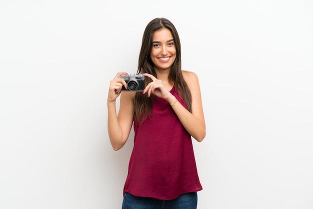 Junge frau über der lokalisierten weißen wand, die eine kamera hält Premium Fotos