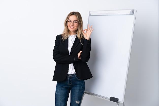 Junge frau über der lokalisierten weißen wand, die okayzeichen mit den fingern zeigt Premium Fotos