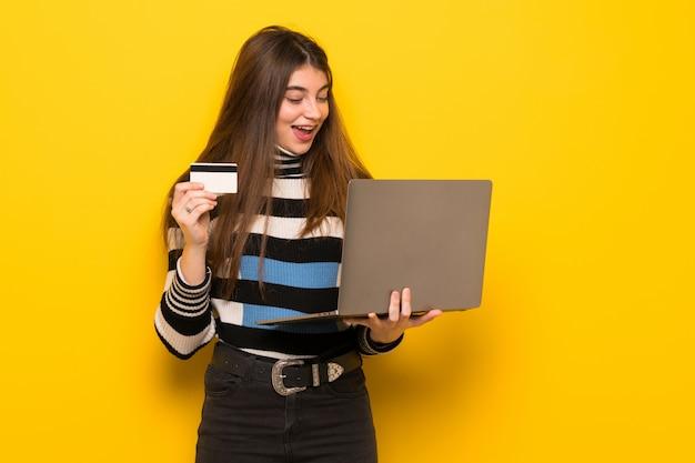 Junge frau über gelber wand mit laptop und kreditkarte Premium Fotos