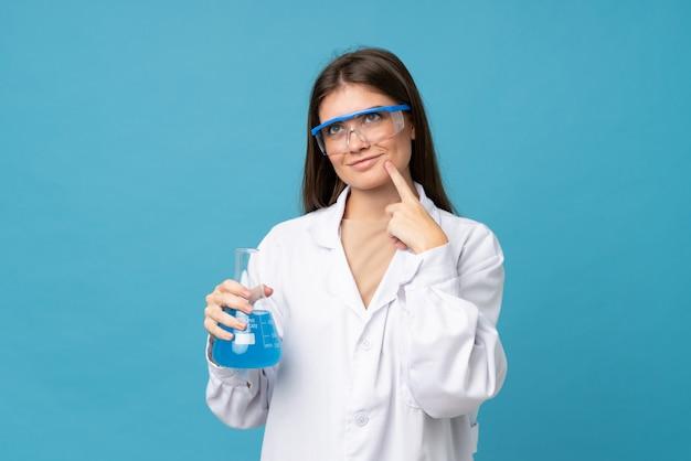 Junge frau über getrenntem blau mit einem wissenschaftlichen reagenzglas Premium Fotos