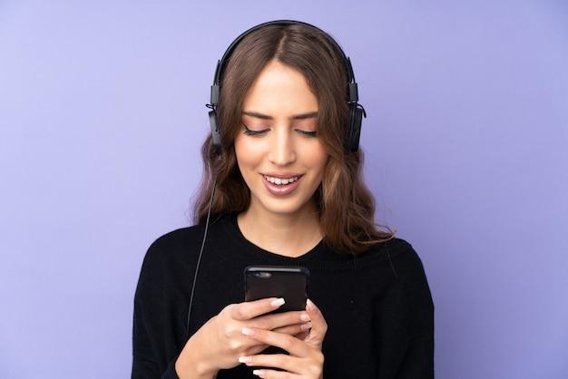 Junge frau über lila wand, die musik hört und auf handy schaut Premium Fotos
