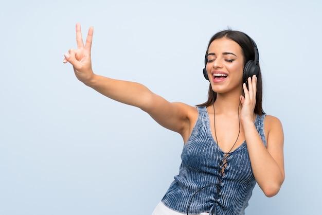 Junge frau über lokalisierter blauer wand hörend musik mit kopfhörern Premium Fotos